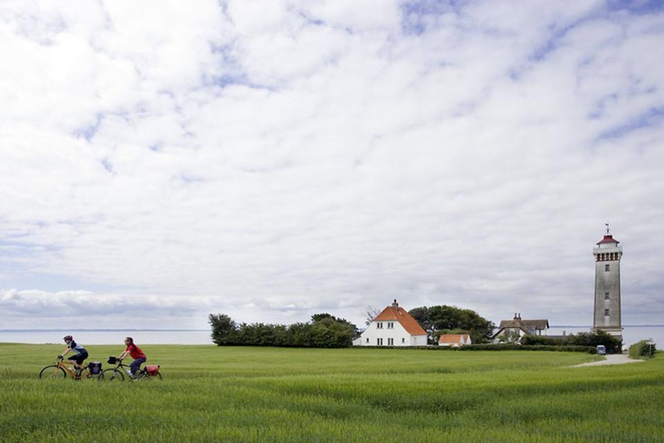 La isla de Fionia , Ciclista y faro en la isla de Fionia , Dinamarca