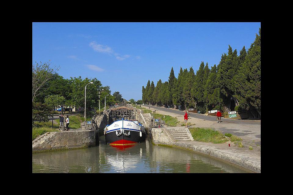 Ce pont, franchissant l'Orb, aide à la navigation des péniches et remédie aussi aux problèmes liés au flux changeant du canal, tantôt en crue, tantôt en sécheresse.