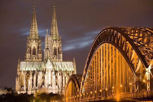 La cattedrale di Colonia e il ponte di Deutz sono illuminati magnificamente di notte.