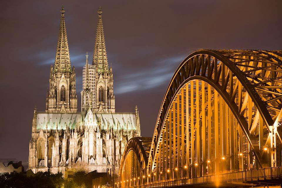 The Cologne Cathedral and the Deutz Bridge are beautifully lit in the evening.