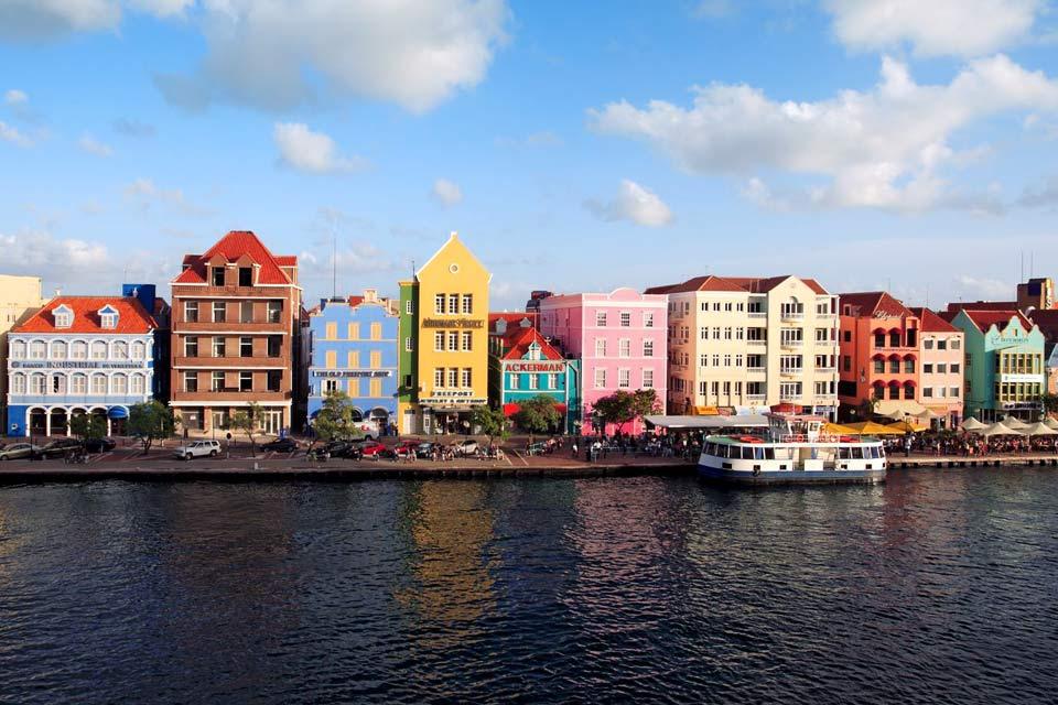 La plus grande des îles, Curaçao, a pour capitale Willemstad. Cette ville à l'atmosphère coloniale se situe sur la côte Sud de l'île. Elle s'étend autour de Schottegat, son immense port naturel. Dans Punda, le vieux quartier, vous longez le Handelskade, le grand quai. Ses maisons, d'architecture néerlandaise, alignent leurs façades à pignons aux tons roses, bleus, jaunes et verts pistache. Juste à ...