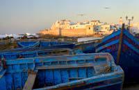 Nichée sur une presqu'île, face à l'océan Atlantique, Essaouira aime surprendre le voyageur. Par son architecture tout d'abord. L'ocre rosé de ses remparts tranche, en effet, avec la blancheur de ses maisons dont les portes et les volets bleus rappellent les îles Grecques. Ses rues parfaitement rectilignes, conçues au XVIIème siècle par le Français Théodore Cornut, en font un exemple unique d'urbanisme ...