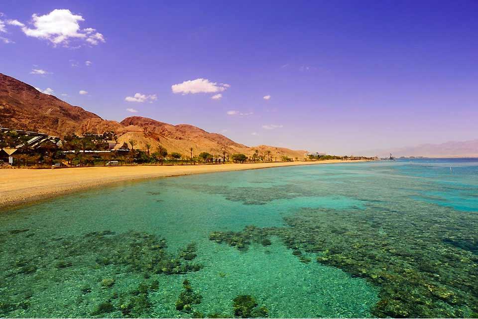 Situada a orillas del mar Rojo, en el extremo sur del país, Eilat es una de las estaciones balnearias más populares de Israel. Rodeada por ambos lados por las montañas púrpura del desierto, en una panorámica que corta el aliento, la localidad ha crecido en pocas décadas sin una verdadera cohesión arquitectónica. El aeropuerto, situado en pleno centro de la ciudad, es una prueba de esta urbanización ...