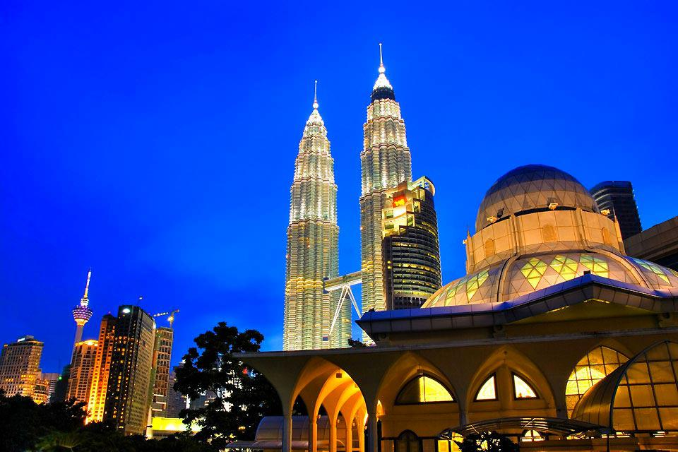 """Kuala Lumpur is an old town, built in the middle of the jungle. It is therefore up to its name, meaning """"muddy river"""". It was given this name by the city's former inhabitants, who settled in the middle of swamps. Therefore, nobody could have tought of these origins when you contemplate what it has become : prestigious buildings or immense towers. These disproportionate buildings emerge everywhere from ..."""