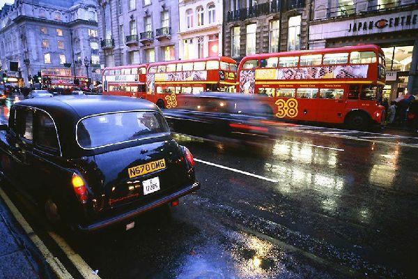 Escena típica londinense con un autobús rojo de dos plantas y un taxi negro.