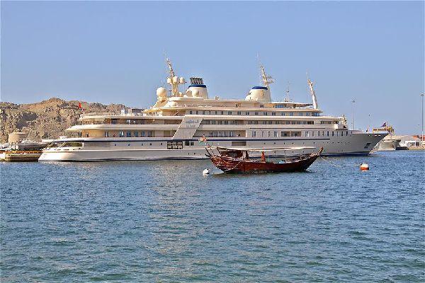 Kontrast zwischen einem traditionellen Dhow und der luxuriösen Jacht des Sultans.