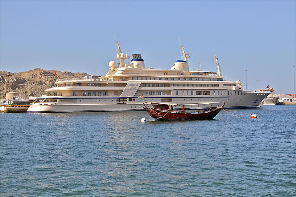 The contrast between the traditional dhow and the sultan's luxurious yacht.