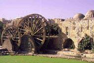 La ville date de l'époque hittite; au premier plan, sur la rivière Oronte, les norias de l'époque séleucide qui alimentaient l'aqueduc.