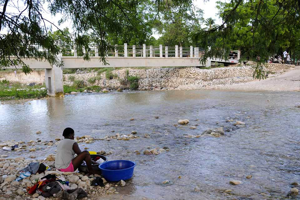 A footbridge crosses the river to Anse-à-Pitres, marking the border with Haiti.