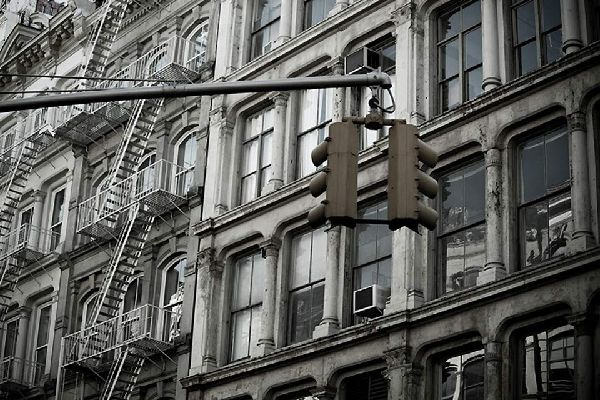 Behind the highly recognisable New York traffic lights, the equally iconic fire escape stairs on many New York apartment blocks in Downtown Manhattan
