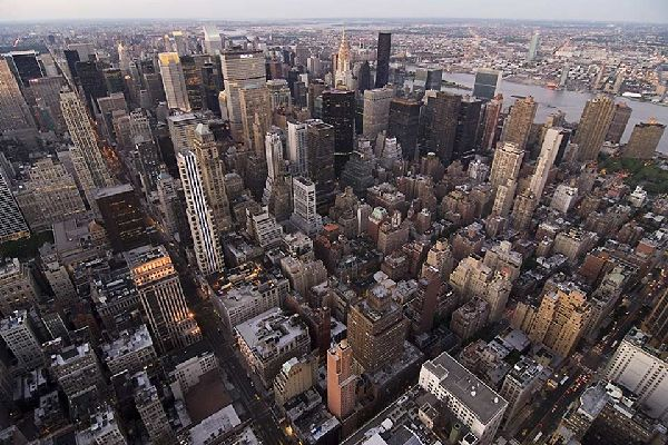 An aerial shot of the skyscrapers of Midtown with the Chrysler Building in the centre and Queens the other side of the East River
