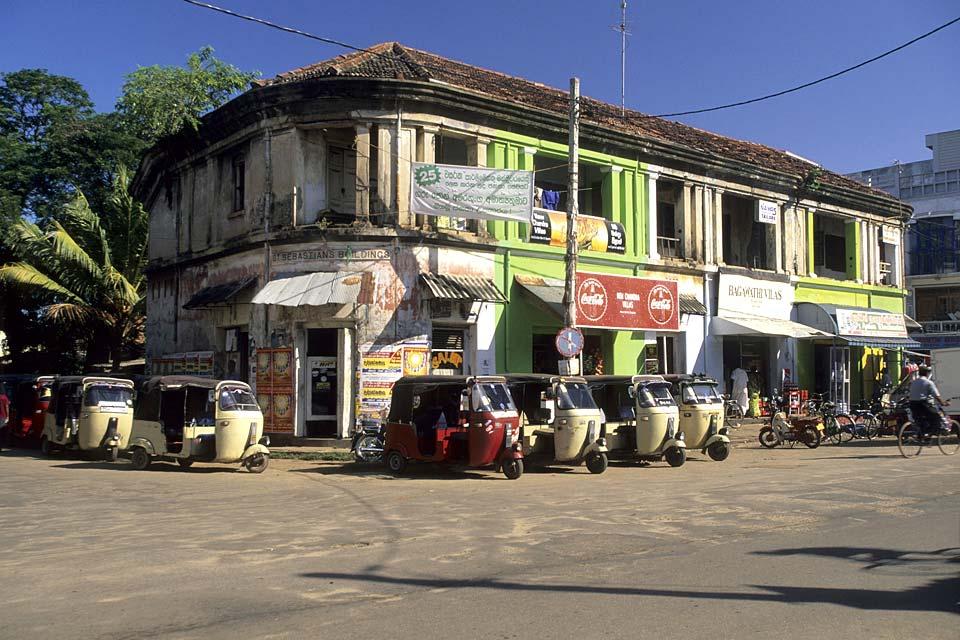 Scène de rue où s'alignent les taxis à trois roues, les touk-touk du Sri Lanka.