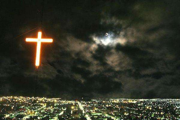 Une croix rose illumine la ville de Bloemfontein pendant la nuit.