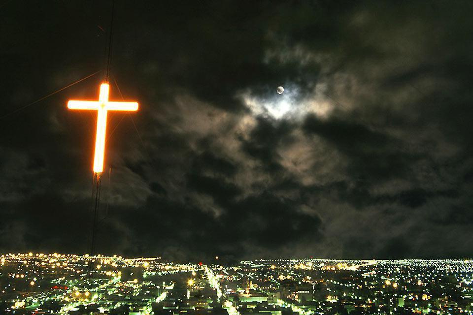 Una croce rosa illumina la città di Bloemfontein durante la notte.