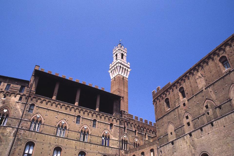 La Torre del Mangia vista desde abajo. Se trata de la atalaya del palacio municipal que debe su nombre al apodo de «Mangiaguadagni» por el que se conocía a su primer guardián.