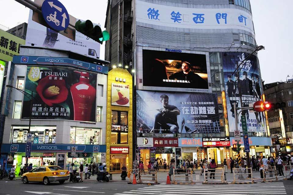 """Le """"Time square"""" de Taïpei. Tours en verre et hôtels de luxe côtoient les publicités colorées et les échoppes grouillantes au ras du sol."""