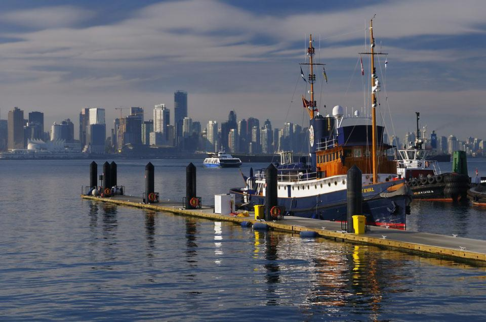 The Vancouver skyline is seen here in the background with a police boat, coal cargo ship and ferry in the foreground