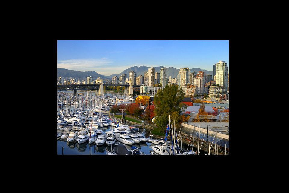 Panorama of boats moored at Granville Island Boat Yard and Burrard Marina with a bridge and coastal mountains in the background