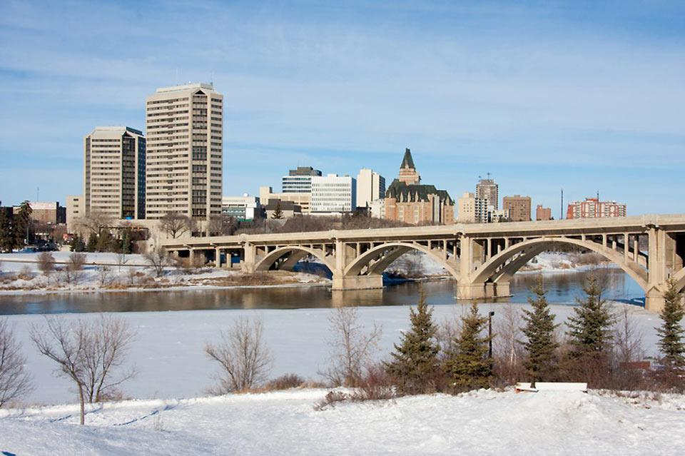 A different perspective of downtown Saskatoon with a bridge over the South Saskatchewan River in the foreground