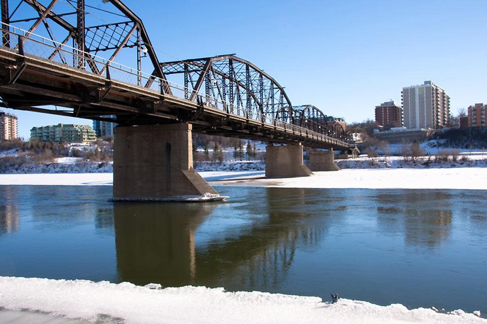 An old bridge over the South Saskatchewan River with the city in the background