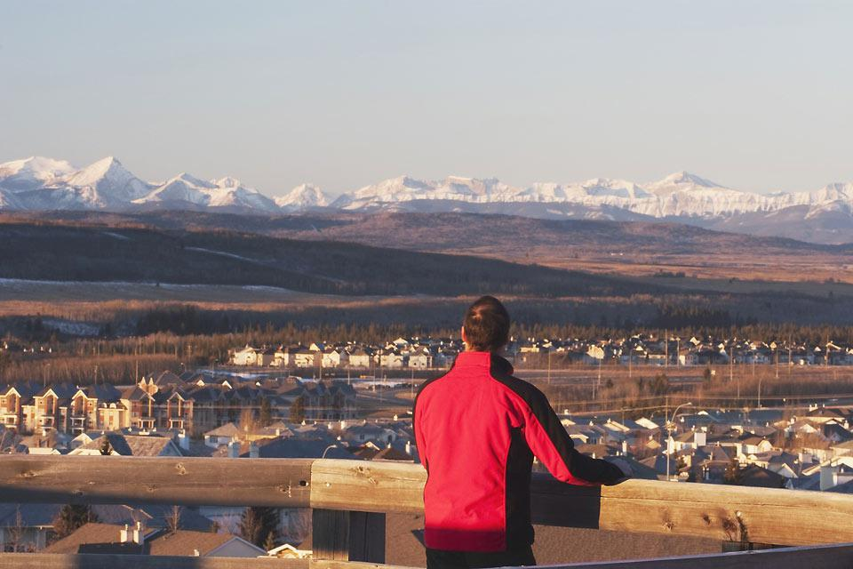 A man looks down over the city with the Rockies in the background
