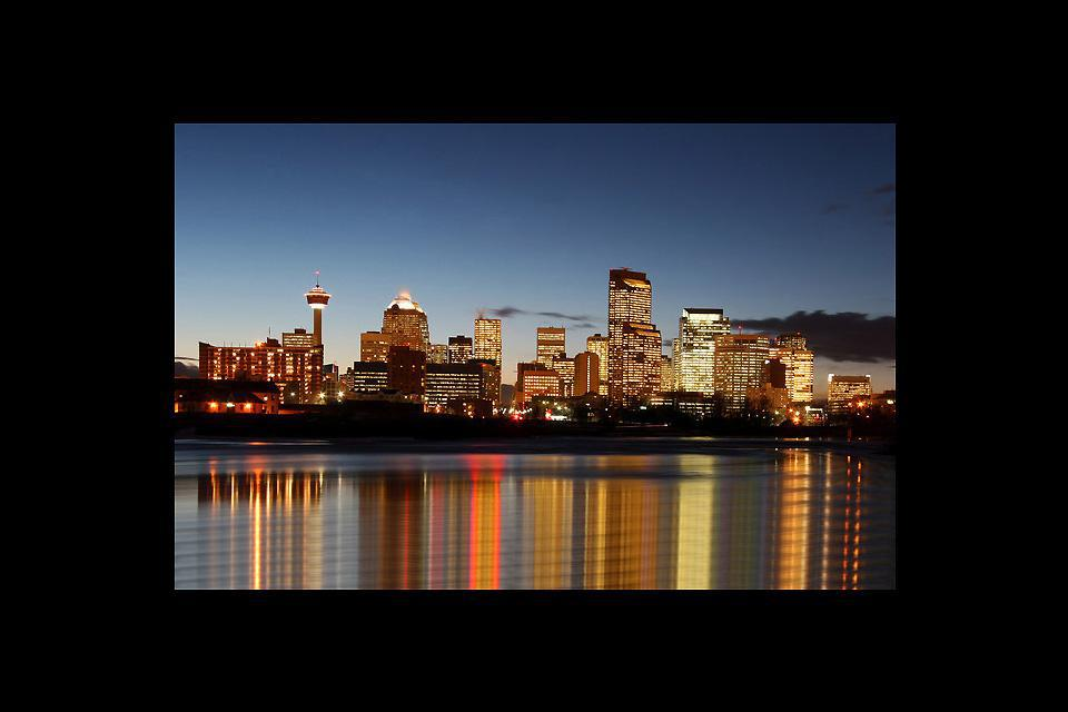 A shot of downtown Calgary at night, its buildings alight, reflected in the river